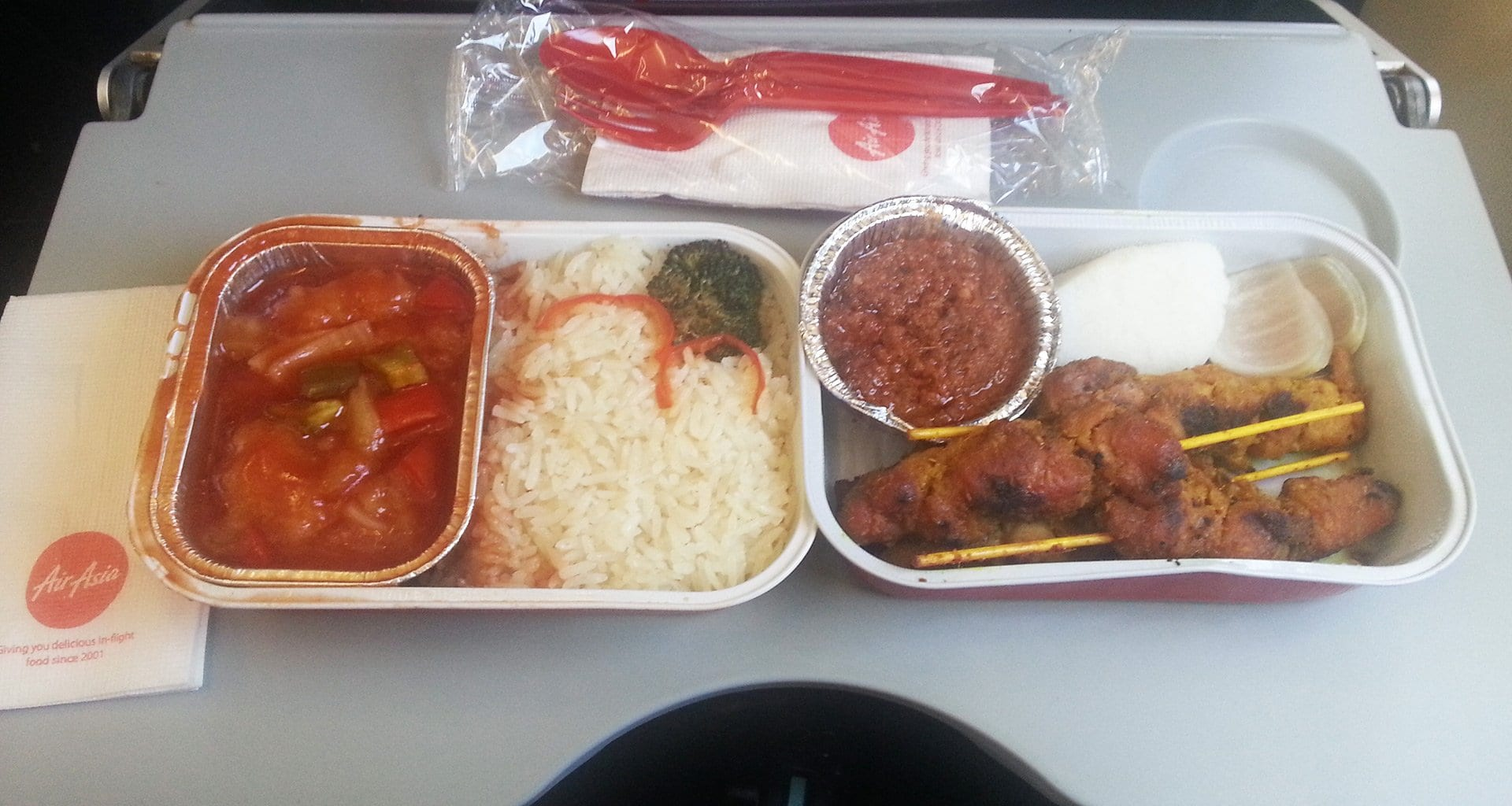 Air Asia meal tray with two hot meals. Chicken stay and sweet and sour fish with rice
