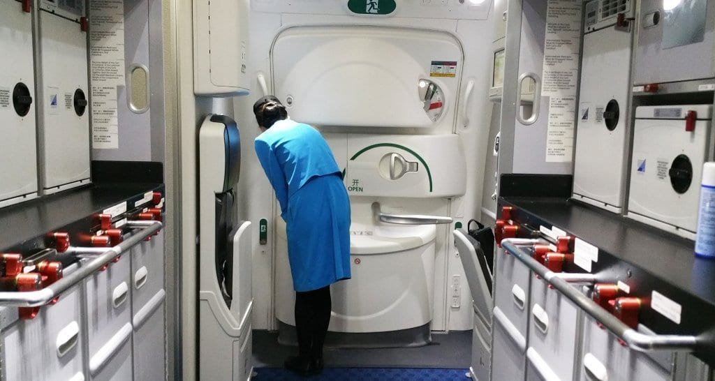 Xiamen Airlines cabin crew member waits to open door
